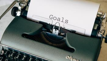 "An olive green typewriter with a sheet of paper stuck in it reading ""Goals"""