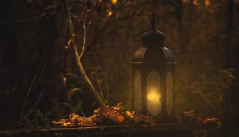 a photo of an iron lantern with a candle in an autumn scene