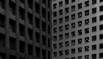 a grey and black apartment building with square windows